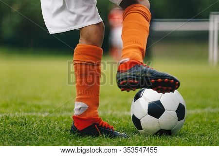 Soccer Ball Kick. Close Up Of Legs And Feet Of Football Player In Red Socks And Cleats Running And D