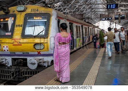 Mumbai, India - February 29, 2020: Indian Woman Wearing A Sari Waits For Her Train At Chatrapati Shi