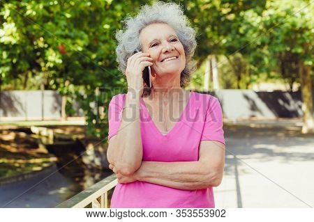 Happy Cheerful Old Lady Talking On Cell In Park. Senior Grey Haired Woman In Casual Standing On Park