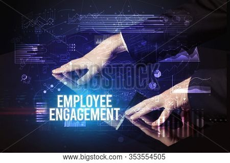 Businessman touching huge screen with EMPLOYEE ENGAGEMENT inscription, cyber business concept
