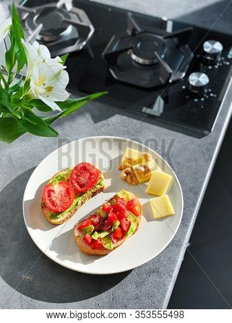 Two sandwiches with fresh vegetables- avocado and tomato, with cashew nuts and cheese on a plate. In the kitchen interior.
