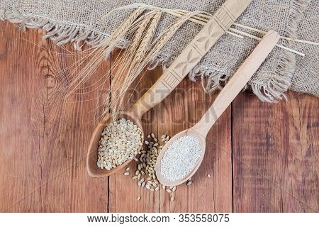 Raw Crushed Barley Groats And Pearl Barley In Two Wooden Spoons, Barley Ears On Burlap On The Rustic