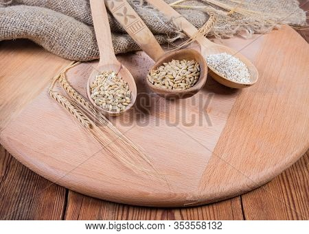 Raw Crushed Barley Groats, Pearl Barley And Whole Barley Grains In Different Wooden Spoons On The Wo