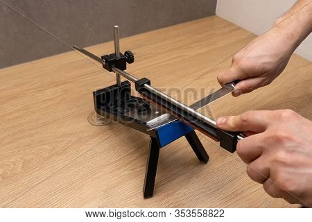Mans Hands Sharpen Dull Steel Knife On Wooden Table At The Kitchen With Professional Knife Sharpener