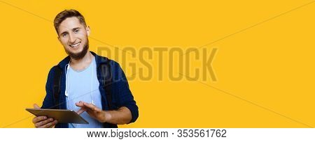 Caucasian Man With Nice Beard And Blue Eyes Is Holding A Tablet While Posing Near The Yellow Freespa