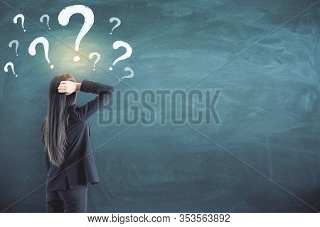 Thoughtful Businesswoman With Drawn Question Marks On Blackboard. Ask And Problem Concept
