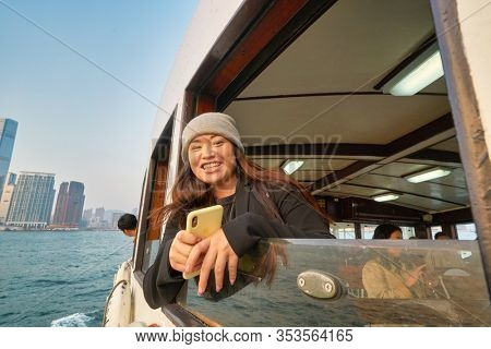 HONG KONG, CHINA - CIRCA JANUARY, 2019: outdoor portrait of a woman on a Star Ferry crossing Victoria Harbour. The Star Ferry is a passenger ferry service operator and tourist attraction in Hong Kong.