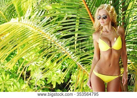 Young female in yellow bikini and sunglasses enjoying sunny day under palm tree on the tropical beach
