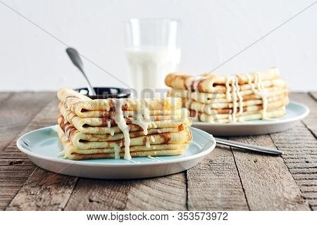 Thin Pancakes, Crepes With  Condensed Milk In A Blue Plate On A Wooden Table.