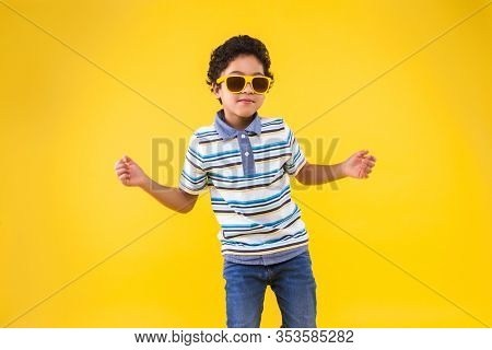 Dark Skinned Curly Smiling Boy In Blue Striped T-shirt Is Listening Music And Dancing On Bright Yell