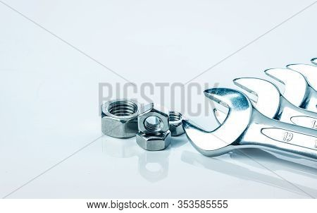 Metal Hexagon Nuts And Chrome Wrenches Isolated On White Background. Mechanic Tools For Maintenance.