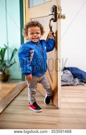 Cute little boy opening the front door to his home. Peeking around with a big smile on his face. Playful fun photo of a 2 year old boy