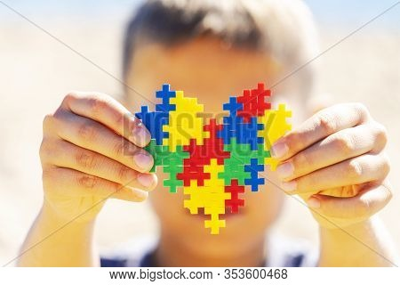 World Autism Awareness Day Concept. Boy Holding Colorful Puzzle Heart In Front Of His Face