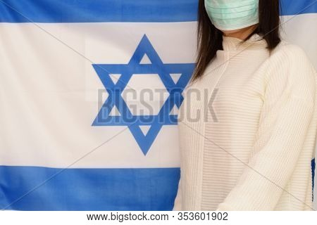 Israeli Woman With Medical Face Mask On Israel Flag Background. Israelis Are In 14-day Quarantine Fo
