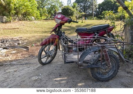 Racha Island, Thailand, January 5, 2020: An Old Rusty Red Japanese Motorbike With A Trailer Or Sidec