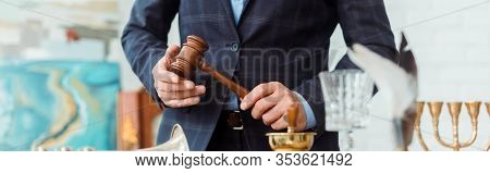 Panoramic Shot Of Auctioneer In Suit Holding Wooden Gavel During Auction
