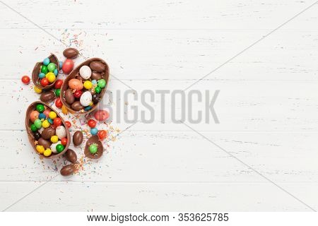 Chocolate easter eggs and colorful sweets on wooden background greeting card. Top view. Flat lay with space for your greetings