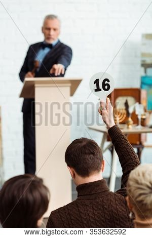 Back View Of Buyer Showing Auction Paddle With Number Sixteen To Auctioneer During Auction