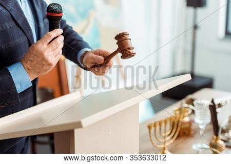 Cropped View Of Auctioneer In Suit Talking With Microphone And Holding Gavel During Auction