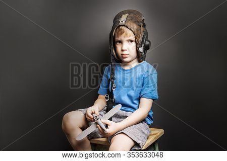 Childrens Dreams: A Little Boy Sits On A Chair In An Old Flight Helmet And With A Scale Model Of An