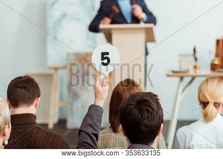 Back View Of Buyer Showing Auction Paddle With Number Five During Auction
