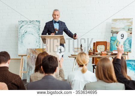 Selective Focus Of Auctioneer Holding Gavel And Microphone And Looking At Buyers During Auction