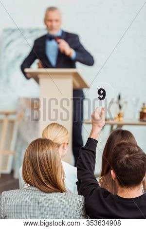 Back View Of Buyer Showing Auction Paddle With Number Nine During Auction