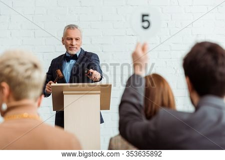 Selective Focus Of Smiling Auctioneer Pointing With Finger At Buyer During Auction
