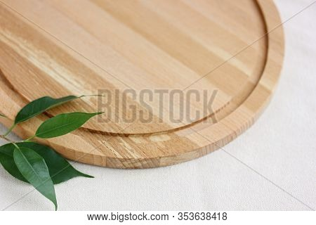 Empty Wooden Cutting Board On A Light Linen Tablecloth And Green Leaves. Light Natural Background, M