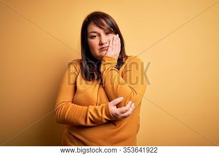 Beautiful brunette plus size woman wearing casual sweater over isolated yellow background thinking looking tired and bored with depression problems with crossed arms.