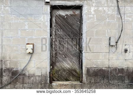 An Old Wood Door On A  Concrete Abandoned Alley Warehouse Building