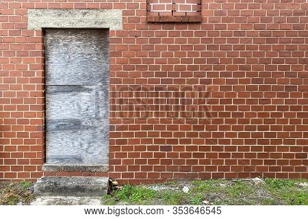 A Boarded Up Door Way On An Abandoned Red Brick Back Alley Warehouse Building
