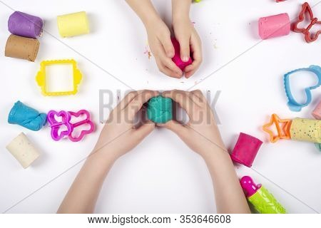 Children Hands Playing With Colorful Modeling Clay On White Background. Educational Game With Clay.