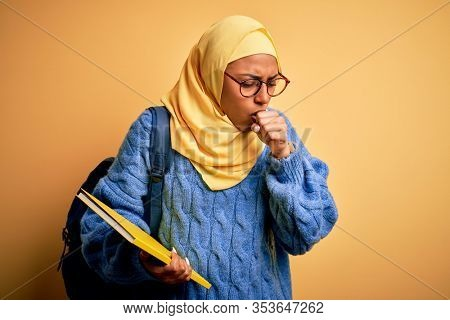 Young African American student woman wearing muslim hijab and backpack holding book feeling unwell and coughing as symptom for cold or bronchitis. Health care concept.