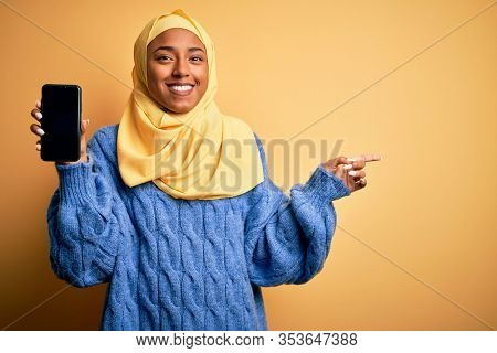 Young African American afro woman wearing muslim hijab showing smartphone very happy pointing with hand and finger to the side