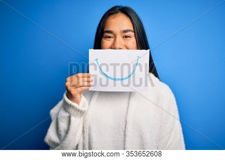 Young beautiful asian woman holding paper with smile draw on mouth over blue background with a happy face standing and smiling with a confident smile showing teeth