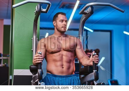 Powerful Athletic Bodybuilder Doing Excersise On A Parallel Bars In A Modern Fitness Center