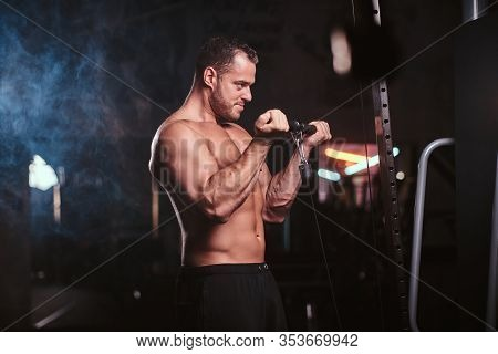 Powerful Adult Bodybuilder Pumping Up His Biceps On A Hand Pull Machine In A Dark Gym Under The Spot
