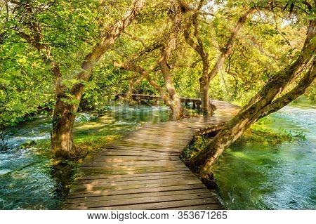 Wooden Boardwalk In The Green Forest Of Krka National Park, Croatia. Beautiful Walking Trail Or Foot