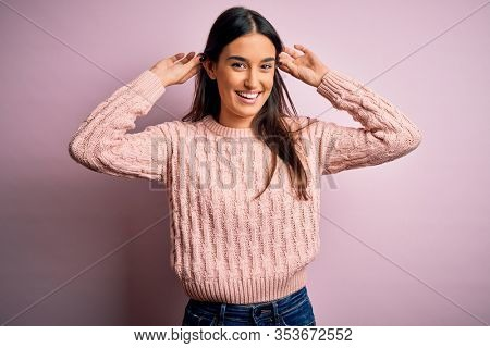 Young beautiful brunette woman wearing casual sweater over isolated pink background Smiling pulling ears with fingers, funny gesture. Audition problem