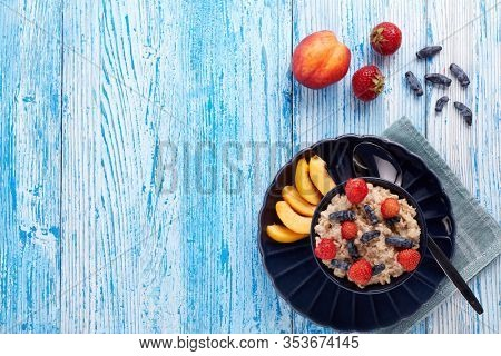 Oatmeal porridge with fresh berries and fruit in dark blue bowl on blue wooden background. Top view with copy space. Concept of healthy lifestyle, healthy food, dieting, vegetarian food