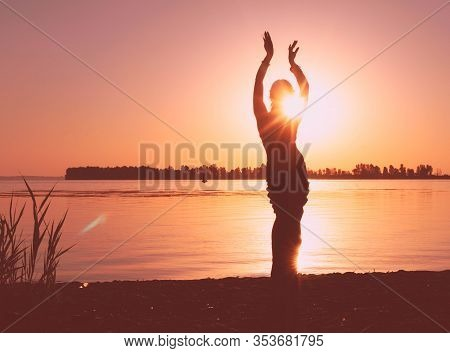 Glowing Silhouette Of Slim Woman With Hands Up In The Air Illuminated With Sunshine In Front Sky Nea