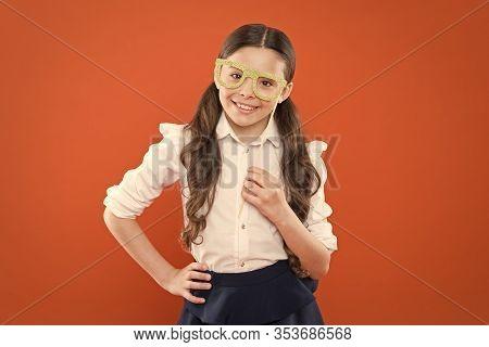 What Does It Mean Being Smart. Little Smart Schoolgirl On Orange Background. Small Kid Wearing Eye G