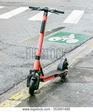 Red Color Rental Electric Scooter On The Sidewalk