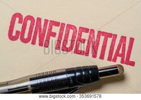 Confidential stamp on a manilla folder with a pen