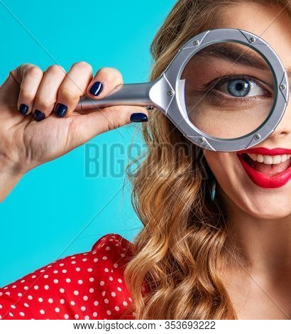 Cheerful blonde holds a magnifying glass in front eye. Young woman holds a magnifying glass in front of her eye. Funny girl with a smile and loupe. Funny girl. Eyesight care. Funny face of a girl
