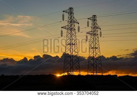 Electric Power Industry And Renewable Energy. Transmission Towers Or Electricity Pylons With Solar E