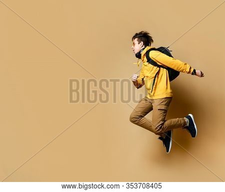 Portrait Of A Young Student Man Jumping In The Studio On A Beige Background.