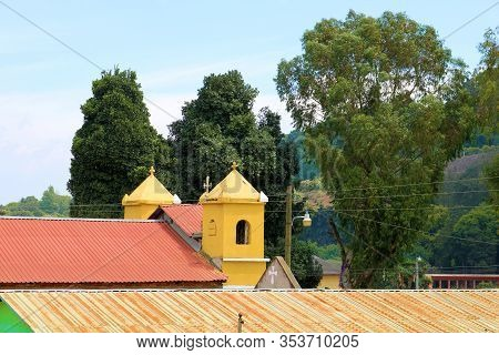 Cathedral Surrounded By Large Trees Taken In The Quaint Mountainous Town Of Escuintla, Guatemala Whe