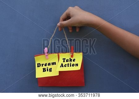 Inspirational Quote - Dream Big. Take Action. With Young Girl Holding Origami Paper Notes Rope Hangi